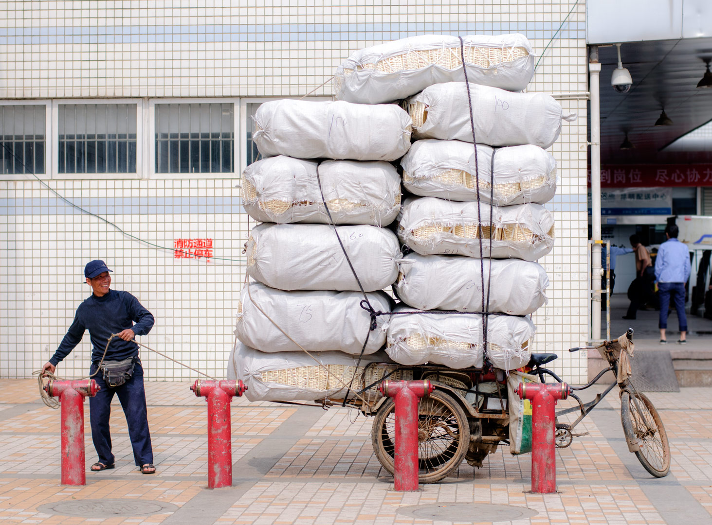 A Chinese man ties huge bags on top of his already overloaded bike rickshaw.